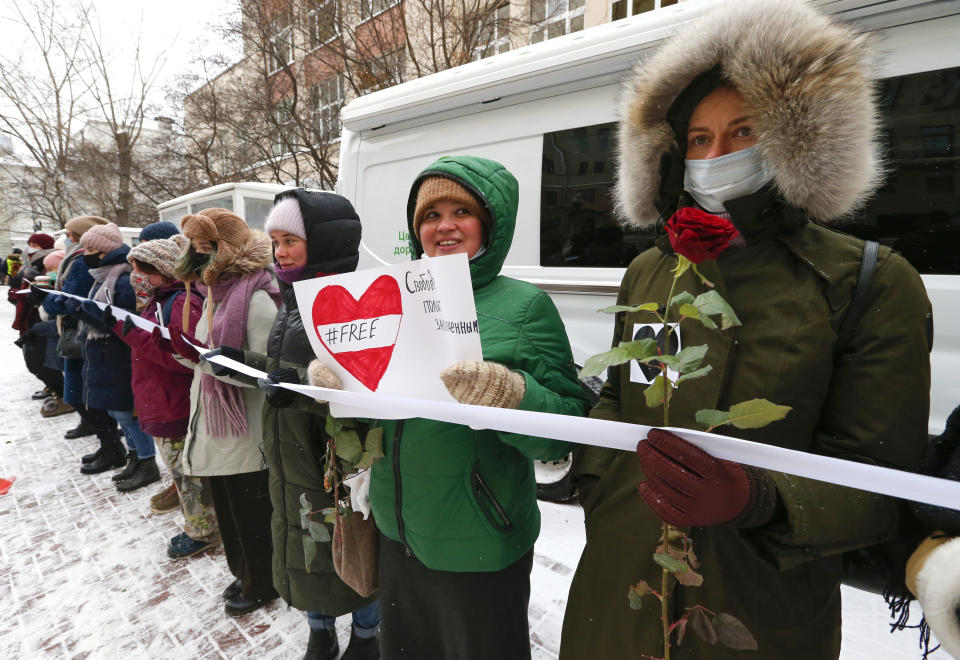 Women, some of them wearing face masks to protect against coronavirus, attend a rally in support of jailed opposition leader Alexei Navalny, and his wife Yulia Navalnaya in Moscow, Russia, Sunday, Feb. 14, 2021. The weekend protests in scores of cities last month over Navalny's detention represented the largest outpouring of popular discontent in years and appeared to have rattled the Kremlin. (AP Photo/Alexander Zemlianichenko)