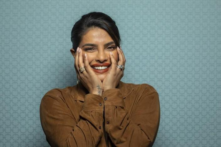 A woman smiles with hands on her face