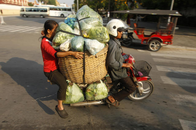 A Cambodian motor-taxi driver carries his costumer and her vegetable goods to the main market in Phnom Penh, Cambodia, Tuesday, Jan. 30, 2018. (AP Photo/Heng Sinith) <span> </span>