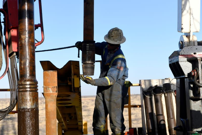 FILE PHOTO: An oil worker removes a thread cap from a piece of drill pipe near Midland, Texas