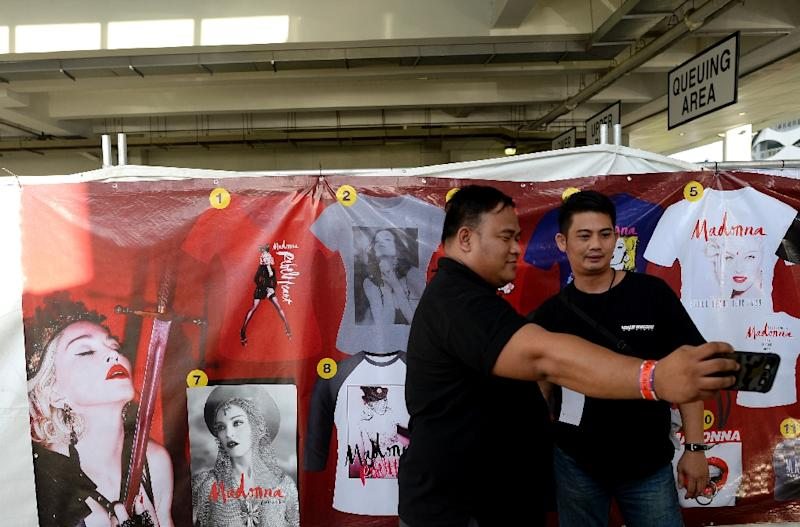 Bouncers take a selfie in front of a poster advertising merchandise for the Madonna concert in Manila on February 24, 2016