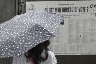 """A woman reads an electoral poster entitled """"Where is my voting station"""" during the second round of the regional elections Sunday, June 27, 2021 in Paris. Paris voting stations that sometimes see lines stood largely empty, other than a few elderly voters. Turnout nationwide was less than 13% by midday. (AP Photo/Rafael Yaghobzadeh)"""