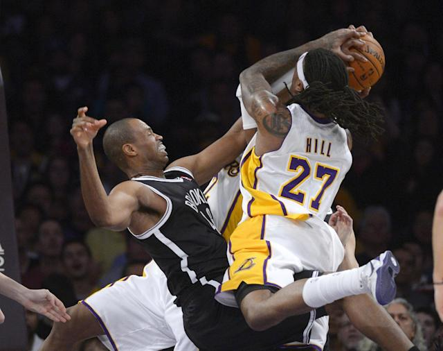Los Angeles Lakers forward Jordan Hill, right, tries to put up a shot as Brooklyn Nets center Jason Collins blocks it during the first half of an NBA basketball, Sunday, Feb. 23, 2014, in Los Angeles. (AP Photo/Mark J. Terrill)