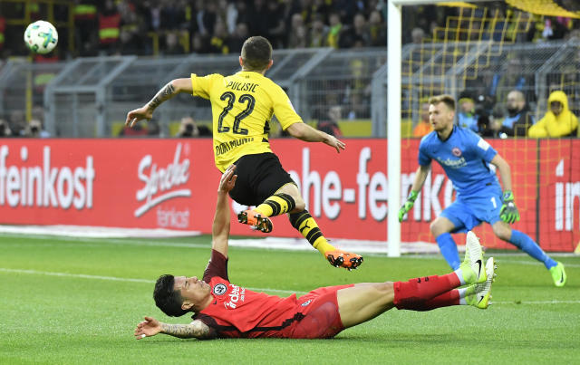 Dortmund's Christian Pulisic jumps over Frankfurt's Carlos Salcedo, passing to Dortmund's Marco Reus who scores the opening goal during the German Bundesliga soccer match between Borussia Dortmund and Eintracht Frankfurt in Dortmund, Germany, Sunday, March 11, 2018. (AP Photo/Martin Meissner)
