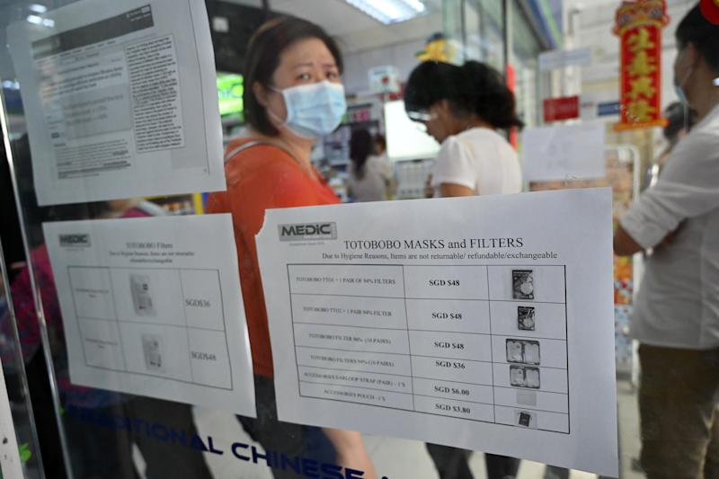 People queue to purchase protective face mask, sanitizer and thermometer at a pharmacy in Singapore on January 29, 2020. - Singapore has so far confirmed seven cases of the novel coronavirus, a virus similar to the SARS pathogen -- all of them arrivals from Wuhan. (Photo by Roslan RAHMAN / AFP) / TO GO WITH China-health-virus-tourism-hotels,SCENE by Sebastien RICCI (Photo by ROSLAN RAHMAN/AFP via Getty Images)