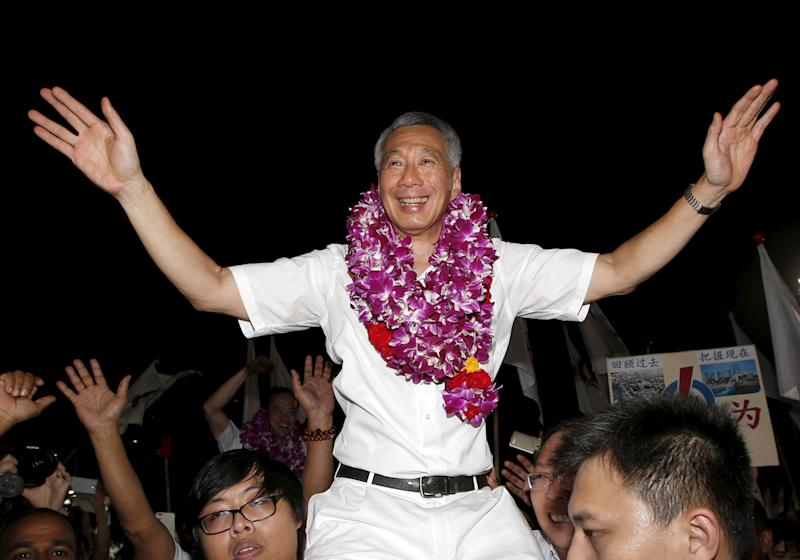Prime Minister and Secretary-General of the People's Action Party Lee Hsien Loong (centre) celebrates with supporters after the general election results at a stadium in Singapore on 12 September, 2015. (Reuters file photo)
