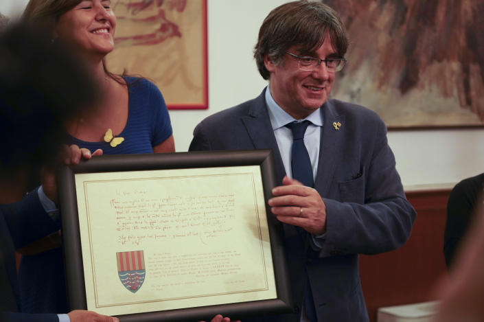 Catalan separatist leader Carles Puigdemont, right, flanked by Speaker of the Catalan Parliament Laura Borras exchanges gifts with Mayor of Alghero Mario Conoci in Alghero, Sardinia, Italy, Saturday, Sept. 25, 2021. Puigdemont was visiting the city hall after he took a leisurely walk in the Sardinian city, waving to supporters, a day after a judge freed him from jail pending a hearing on his extradition to Spain, where the political firebrand is wanted for sedition. (AP Photo/Andrea Rosa)