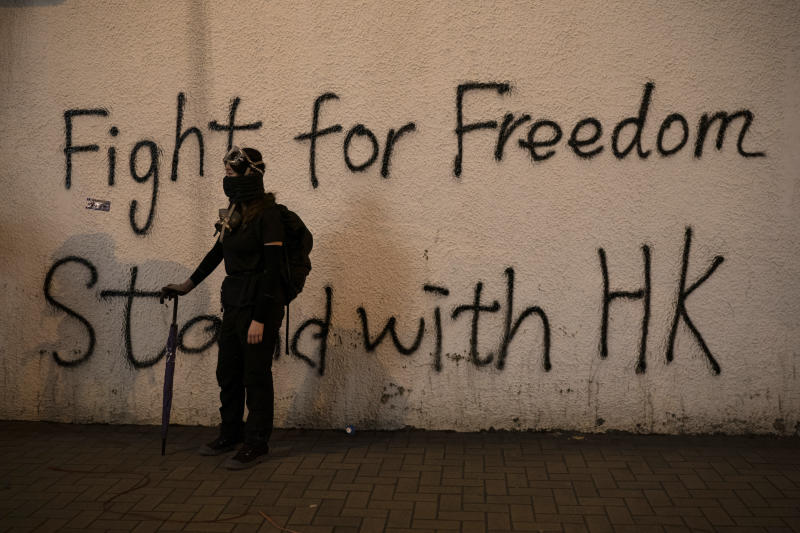 A black-clad protestor stands by graffiti on the wall in Hong Kong, Oct. 1, 2019. (Photo: Felipe Dana/AP)