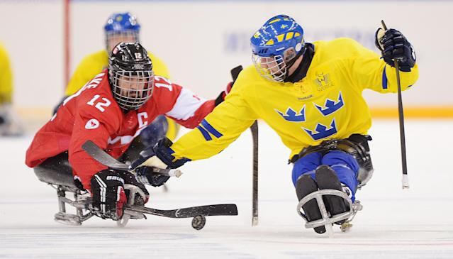 SOCHI, RUSSIA - MARCH 08: Greg Westlake (L) of Canada and Niklas Rakos of Sweden battle for the puck during the Preliminary Round Group A match between Canada and Sweden at Shayba Arena on March 8, 2014 in Sochi, Russia. (Photo by Dennis Grombkowski/Getty Images)