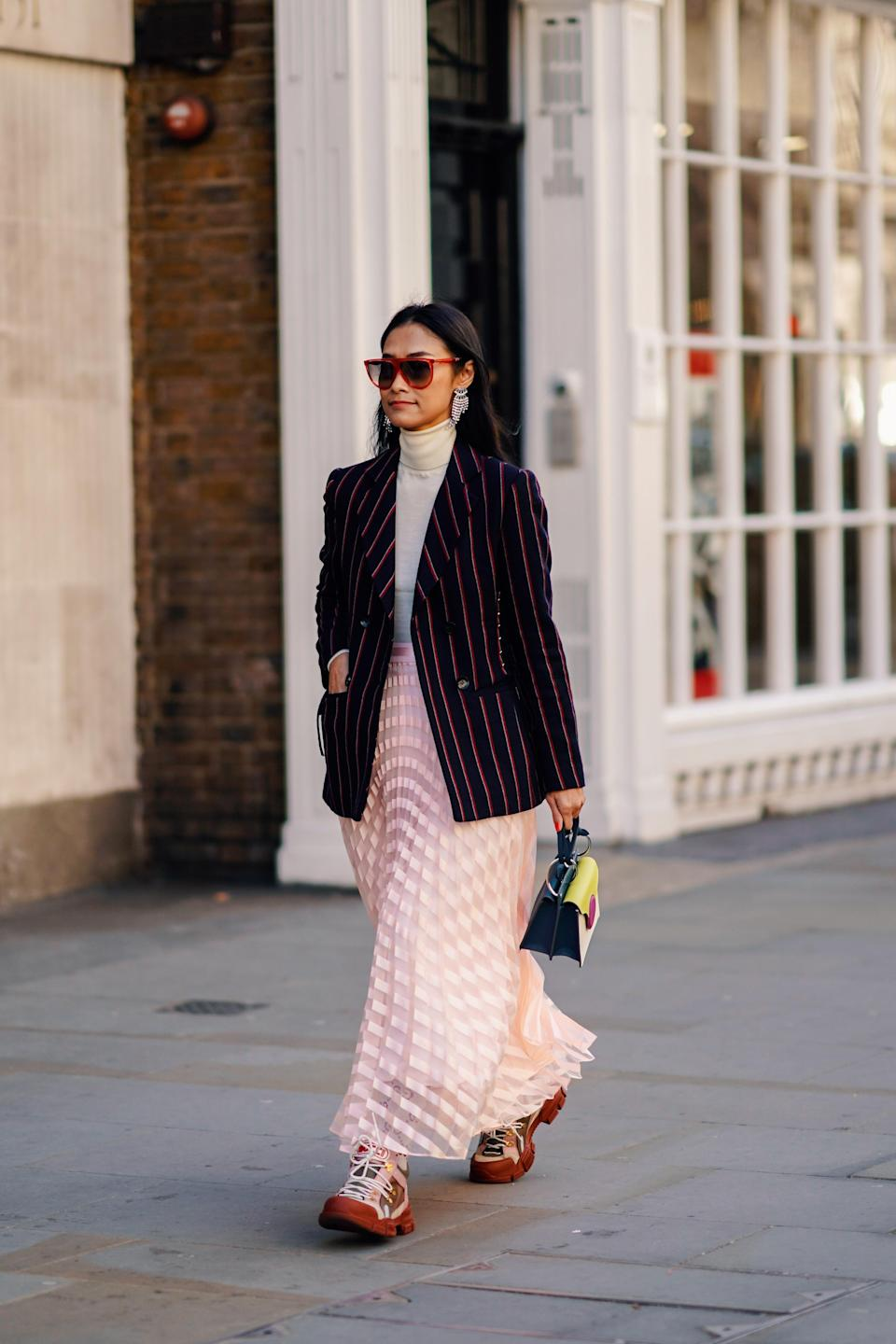 <p>A guest photographed at London Fashion Week in a chic turtleneck, sheer skirt and chunky dad trainers. <em>[Photo: Getty]</em> </p>