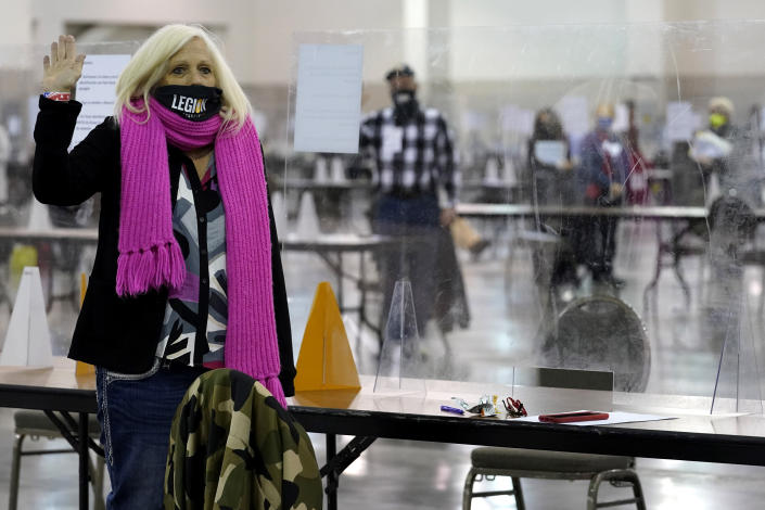 A recount observer takes an oath for a Milwaukee hand recount of Presidential votes at the Wisconsin Center, Friday, Nov. 20, 2020, in Milwaukee, Wis. The recount of the presidential election in Wisconsin's two most heavily Democratic counties began Friday with President Donald Trump's campaign seeking to discard tens of thousands of absentee ballots that it alleged should not have been counted. (AP Photo/Nam Y. Huh)