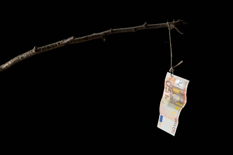 A fifty Euro banknote dangling from a crude fishing rod (Photo: Caspar Benson via Getty Images)