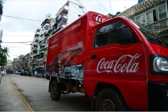 A Coca-Cola truck parked on the street out in front of businesses.