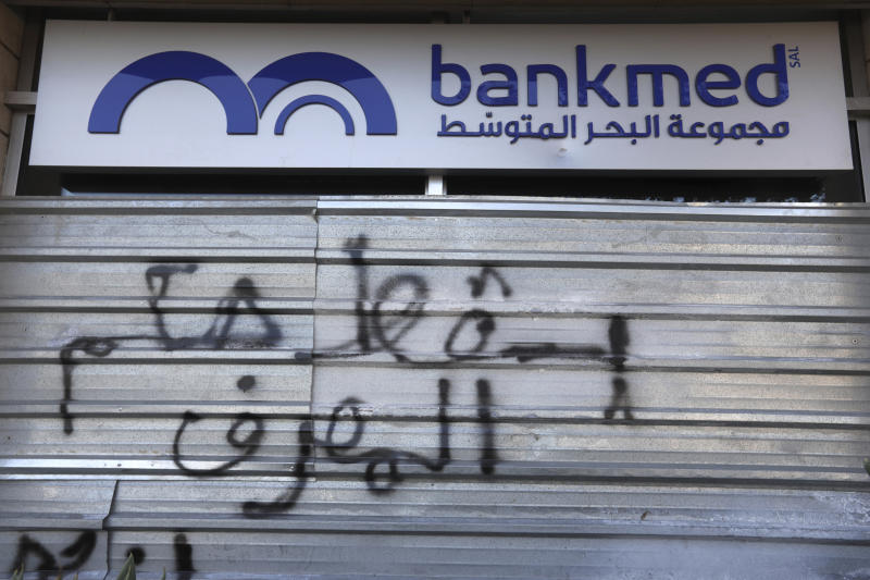 """A door of a closed bank is spray painted with a message in Arabic that reads, """"Down with the rule of the banks,"""" in Beirut, Lebanon, Tuesday, Nov. 12, 2019. Lebanon's banking association says banks will stay closed due to a strike by employees, as country's financial crisis worsens. (AP Photo/Hassan Ammar)"""