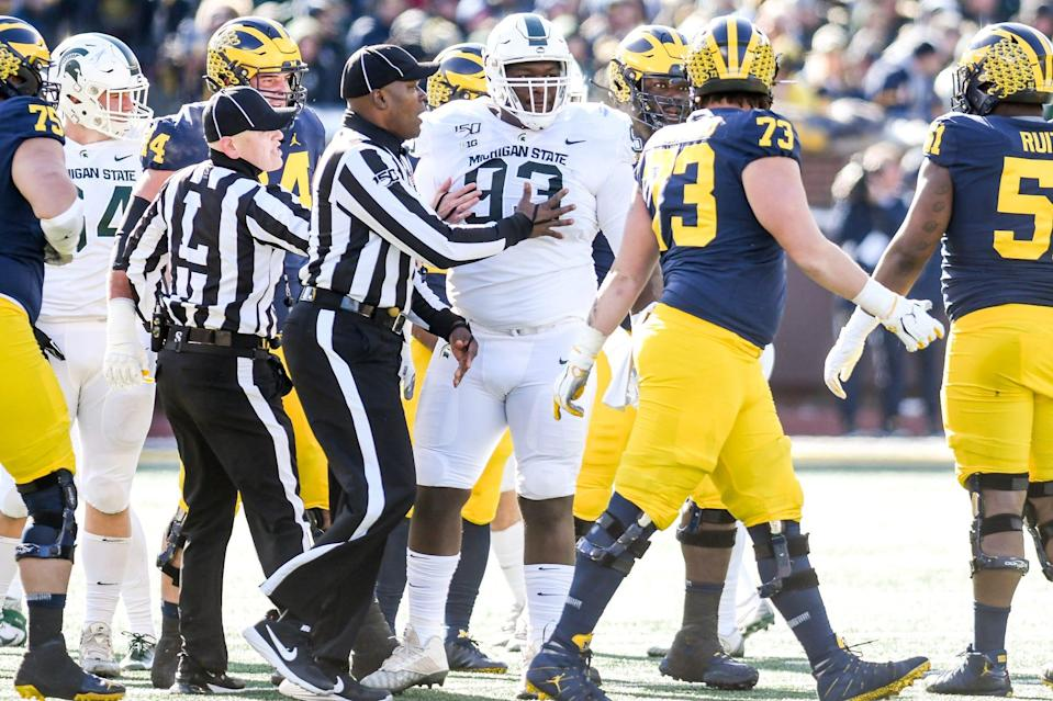 Michigan State's Naquan Jones, center, jaws with Michigan's Jaylen Mayfield after a play during the first quarter on Saturday, Nov. 16, 2019, at Michigan Stadium in Ann Arbor.