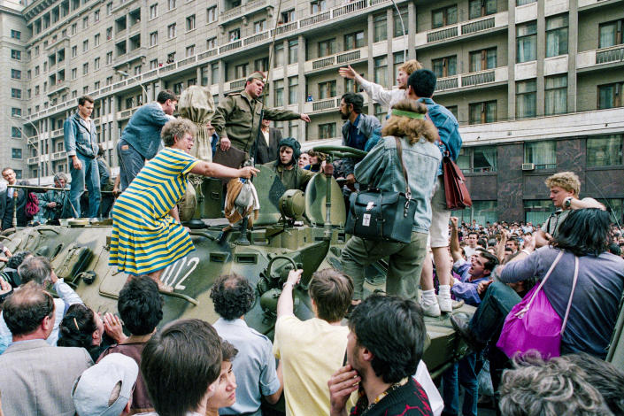 FILE - In this Monday, Aug. 19, 1991 file photo, a crowd gathers around a personnel carrier as some people climb aboard the vehicle and try to block its advance near Red Square in downtown Moscow, Russia. When a group of top Communist officials ousted Soviet leader Mikhail Gorbachev 30 years ago and flooded Moscow with tanks, the world held its breath, fearing a rollback on liberal reforms and a return to the Cold War confrontation. But the August 1991 coup collapsed in just three days, precipitating the breakup of the Soviet Union that plotters said they were trying to prevent. (AP Photo/Boris Yurchenko, File)