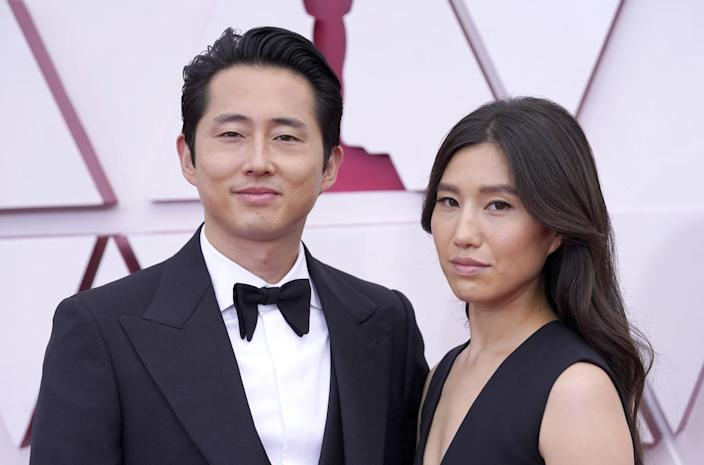 Steven Yeun in a tuxedo and Joana Pak in a dark dress