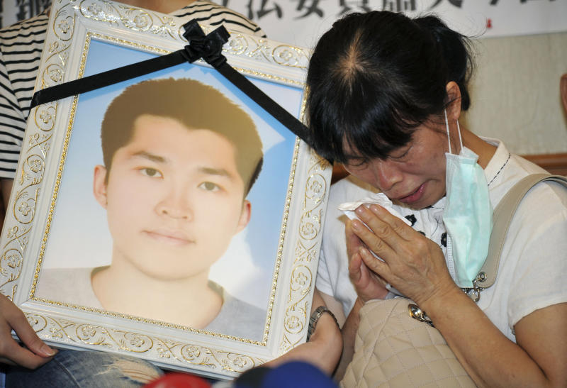 In this photo taken on July 17, 2013, Hu Su-tseng, the mother of Taiwan soldier Hung Chung-chiu, who died after strenuous calisthenics on a base in suburban Taipei, wipes away her tears next to his portrait during a press conference at the legislature in Taipei, Taiwan. The death of the 24-year-old soldier has set off a wave of anger on the democratic island of 23 million people, further undermining the already unpopular administration of President Ma Ying-jeou, and raising hard questions about the future of the island's military. (AP Photo)