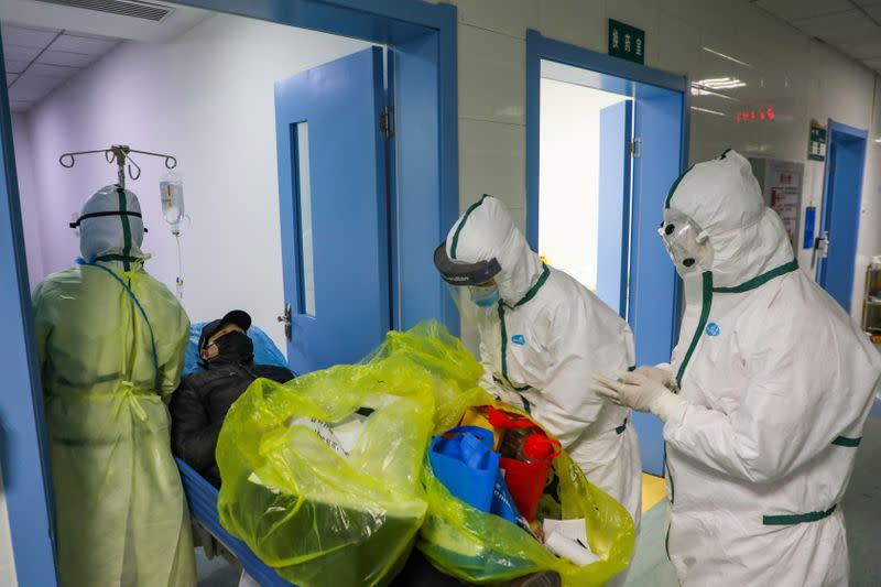 Medical workers in protective suits move a novel coronavirus patient at an isolated ward of a designated hospital in Wuhan