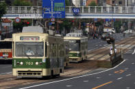 Trams are seen on a street in Hiroshima, western Japan, Monday, Aug. 3, 2020. A tram which survived the Hiroshima atomic bombing will run, without any passenger, on the streets on Aug. 6 to commemorate the day of atomic bombing in the city. (AP Photo/Eugene Hoshiko)