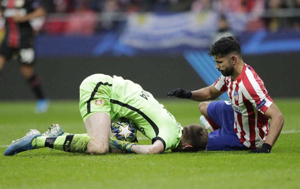 Leverkusen's goalkeeper Lukas Hradecky, left, fights for the ball against Atletico Madrid's Diego Costa during the Champions League Group D soccer match between Atletico Madrid and Bayer Leverkusen at Wanda Metropolitano stadium in Madrid, Spain, Tuesday, Oct. 22, 2019. (AP Photo/Bernat Armangue)