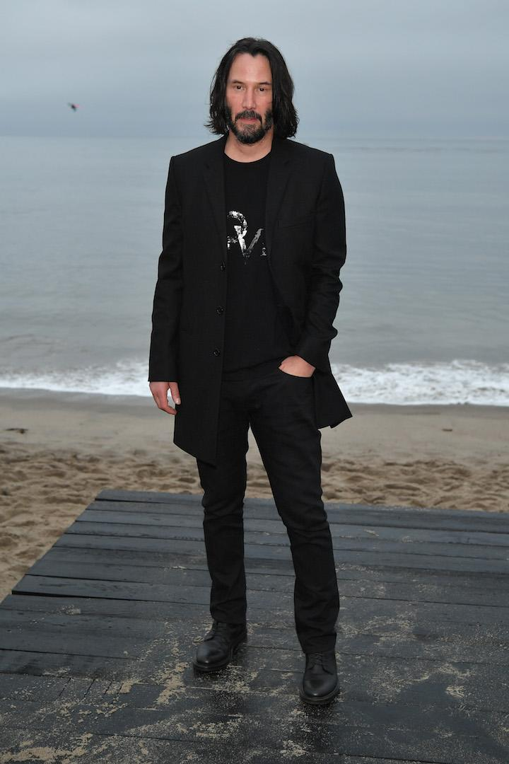 Actor Keanu Reeves also posed for the beach photo call ahead of the SS20 Saint Laurent show in an all-black ensemble. <em>[Photo: Getty]</em>