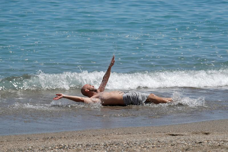 A man relaxes in the water in Malaga (REUTERS)