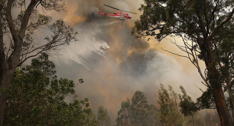 A water bombing helicopter attacks a bushfire near houses along Old Bar road in Old Bar, NSW, Saturday, November 9, 2019. Two people have been killed and seven others are missing in bushfires in NSW which have also destroyed at least 100 homes. (AAP Image/Darren Pateman) NO ARCHIVING