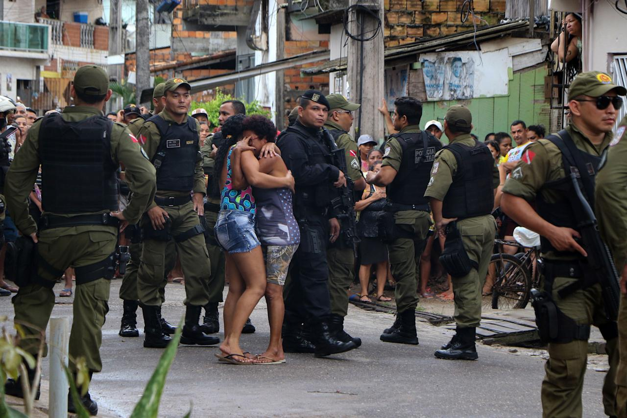 Residents mourn surrounded by police officers outside a bar as corpses are removed after a shooting, in Belem, Para state, Brazil on May 19, 2019. (Photo: Claudio Pinheiro/AFP/Getty Images)