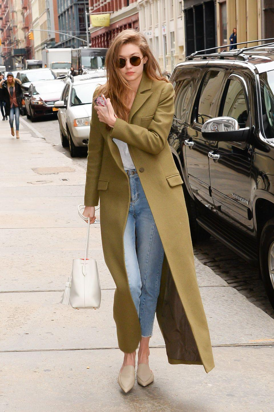 <p>In a floor-length olive green coat, white tee, Sandro high-waisted jeans, pointed-toe flats, white Mansur Gavriel bucket bag and Sunday Somewhere round sunglasses while out in New York.</p>
