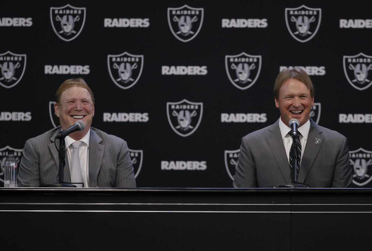 Oakland Raiders coach Jon Gruden, right, smiles as he sits next to owner Mark Davis during a press conference in January. (AP)