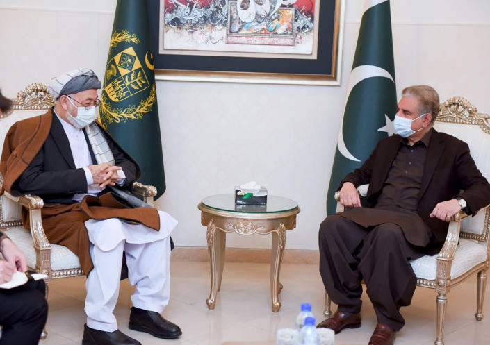In this photo provided by Pakistan's Ministry of Foreign Affairs, Karim Khalili, left, an influential Afghan Shiite leader, meets with Pakistani Foreign Minister Shah Mahmood Qureshi at Foreign Ministry in Islamabad, Pakistan, Tuesday, Jan. 12, 2021. Khalili is visiting Pakistan where members of the minority sect are still reeling from the brutal killing of 11 Shiite coal miners, nine of whom were Afghan immigrants, earlier this month. (Ministry of Foreign Ministry via AP)
