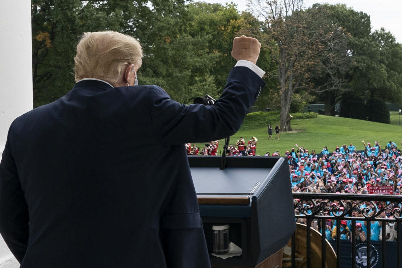 President Donald Trump pumps his fist to the crowd with a bandages on his hand, before speaking from the Blue Room Balcony of the White House to a crowd of supporters, Saturday, Oct. 10, 2020, in Washington.