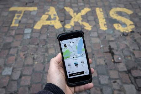 FILE PHOTO: A photo illustration shows the Uber app on a mobile telephone, as it is held up for a posed photograph, in London