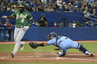 Oakland Athletics' Starling Marte (2) scores ahead of a tag by Toronto Blue Jays catcher Alejandro Kirk during the fifth inning of a baseball game Friday, Sept. 3, 2021, in Toronto. (Jon Blacker/The Canadian Press via AP