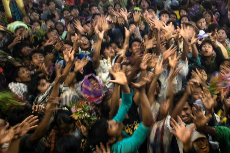 Devotees scramble to grab money thrown into the crowd by wealthy participants inside a shrine during the Ko Gyi Kyaw Nat festival