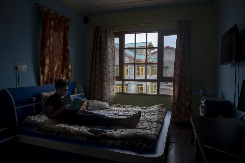 Humzah Mir studies inside his bedroom in Srinagar, Indian controlled Kashmir, Friday, July 17, 2020. Schools in the disputed region reopened after six months in late February, after a strict lockdown that began in August 2019, when India scrapped the region's semi-autonomous status. In March schools were shut again because of the coronavirus pandemic. Humzah, who cleared his grade X exams a few days ago, says it will be a hard road ahead with no proper classes. (AP Photo/Dar Yasin)