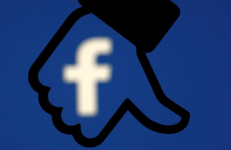 A 3D-printed Facebook dislike button is seen in front the Facebook logo, in this illustration