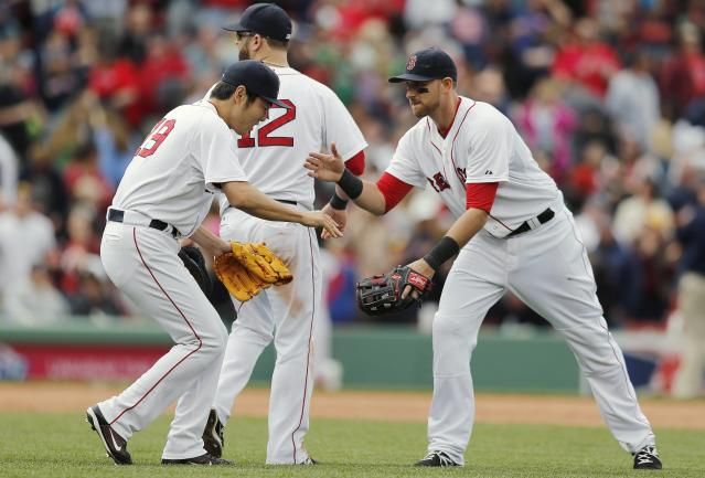 Boston Red Sox's Koji Uehara (19) and Will Middlebrooks, right, celebrate behind teammate Mike Napoli (12) after defeating the Oakland Athletics 6-3 in a baseball game in Boston, Saturday, May 3, 2014. (AP Photo/Michael Dwyer)
