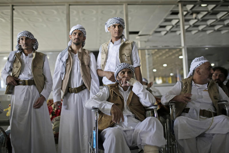 Yemeni prisoners wait for their relatives during their arrival after being released by the Saudi-led coalition in the airport of Sanaa, Yemen, Thursday, Nov. 28, 2019. The International Committee of the Red Cross says over a hundred rebel prisoners released by the Saudi-led coalition have returned to Houthi-controlled territory in Yemen, a step toward a long-anticipated prisoner swap between the warring parties. (AP Photo/Hani Mohammed)