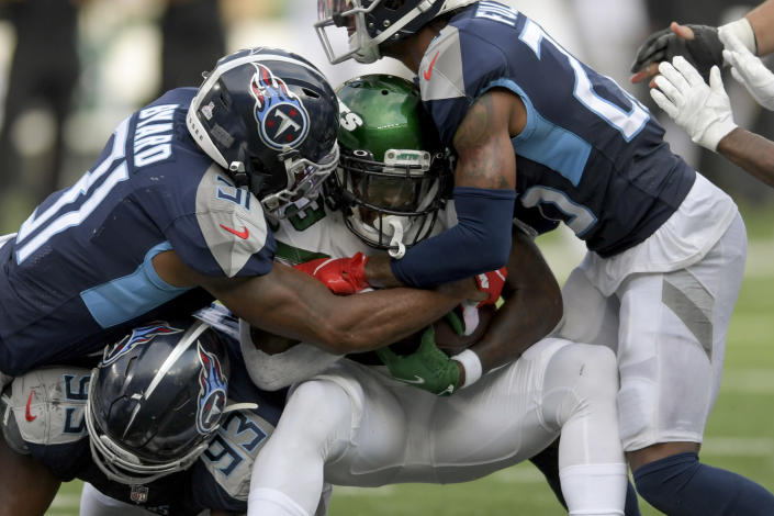 New York Jets running back Tevin Coleman, center, is tackled by Tennessee Titans free safety Kevin Byard (31) during overtime of an NFL football game, Sunday, Oct. 3, 2021, in East Rutherford, N.J. (AP Photo/Bill Kostroun)