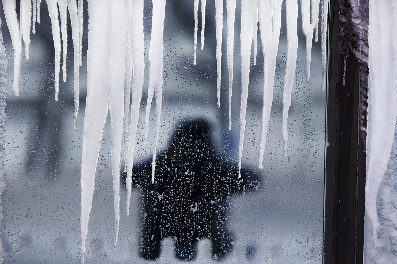 SQUANTUM, MA - FEBRUARY 9: Icicles on a closed restaurant frame those walking around Marina Bay after the Blizzard of 2013. (Photo by Stan Grossfeld/The Boston Globe via Getty Images)