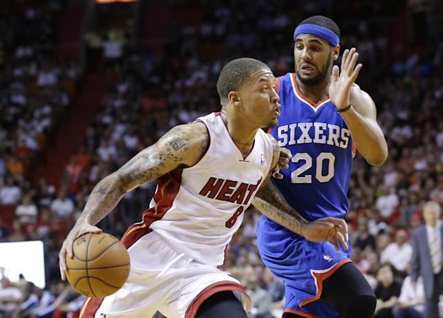 Miami Heat forward Michael Beasley (8) drives to the basket past Philadelphia 76ers forward Brandon Davies (20) during the first half of an NBA basketball game on Wednesday, April 16, 2014, in Miami. (AP Photo/Wilfredo Lee)