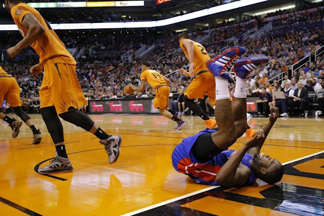 Detroit Pistons' Rodney Stuckey, right, falls after shooting as the Phoenix Suns push the ball up court during the first half of an NBA basketball game, Friday, March 21, 2014, in Phoenix. (AP Photo/Matt York)