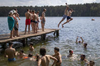 People enjoy the warm weather near a lake near Vilnius, Lithuania, Sunday, June 20, 2021. The hot weather continues in Lithuania as temperatures reached 33 degrees Celsius (91,40 degrees Fahrenheit). (AP Photo/Mindaugas Kulbis)