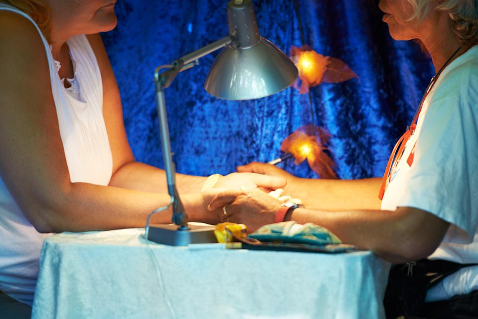 A fortune-teller reading a client's palm. Psychics don't like to give advice on lottery numbers.