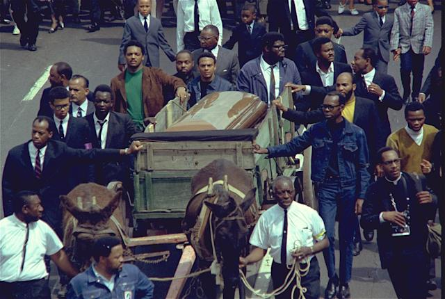 <p>A brace of plow mules draws the farm wagon bearing the mahogany casket of Dr. Martin Luther King Jr. Rev. Jesse Jackson, in green, and Andrew Young, at the left corner of the casket, are among the mourners. (Photo: AP) </p>