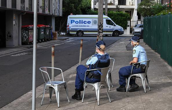 Police officers wearing face masks guard the rear entrance of the Urban Newtown hotel where quarantined Australian travellers who have landed back into Sydney will remain for 14 days.