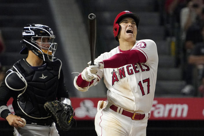 Los Angeles Angels' Shohei Ohtani, right, yells as he strikes out as Colorado Rockies catcher Dom Nunez stands at the plate during the seventh inning of a baseball game Monday, July 26, 2021, in Anaheim, Calif. (AP Photo/Mark J. Terrill)