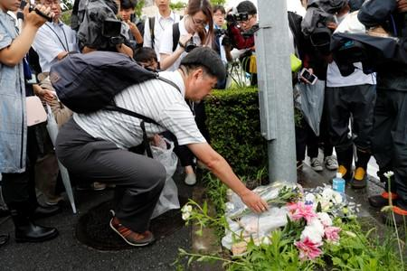A man placed flowers near the torced Kyoto Animation building to mourn the victims of the arson attack in Kyoto